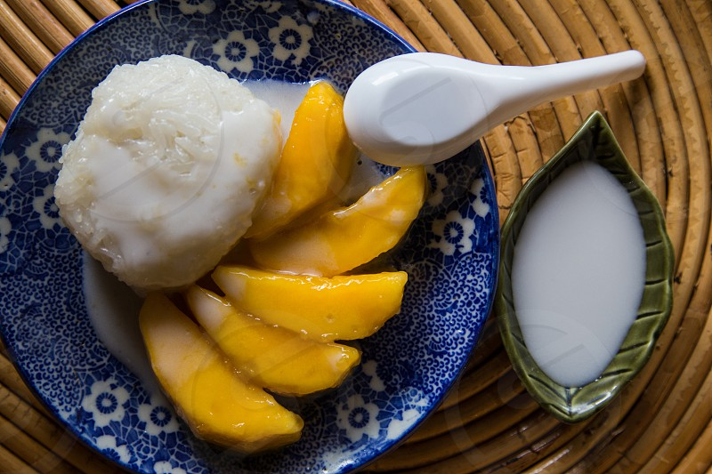 Khao Neeo Mamuang mango with sticky rice and coconut cream is a  classic Thai dessert.  This classic sweet is often served as street food where it is s typically taken home as a treat for the family as it can be messy to eat on the street.  It has become popular overseas as well and a staple in any decent Thai restaurant worthy of the name. photo