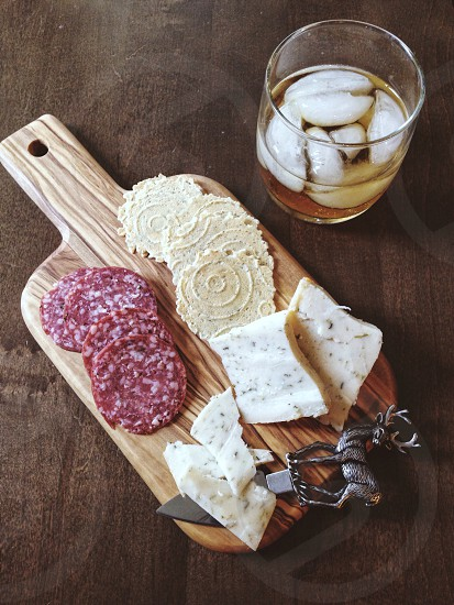 silver deer cheese knife on a wood cutting board with sliced cheese and salami on a table with a drink on teh rocks photo