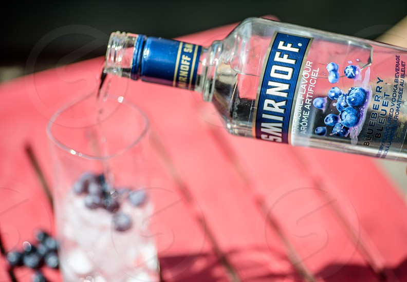 person pouring smirnoff blueberry in clear drinking glass wit blueberries in tilt shift lens photo