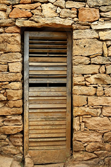 aged weathered wood door on masonry stone wall balearic islands photo