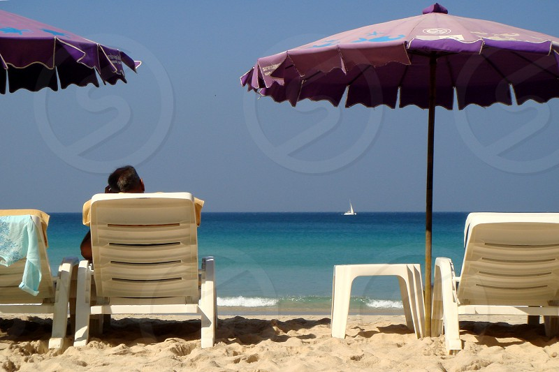 Sunbeds and parasols on the sandy beach photo