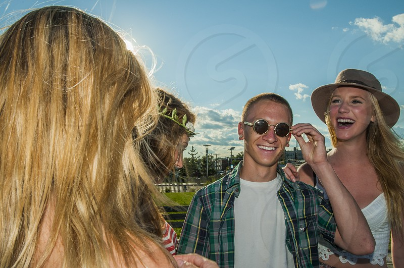 smiling man in white crew neck shirt and green black and gray plaid button up t-shirt touching his round framed sunglasses near 3 women under blue and white sunny cloudy sky photo