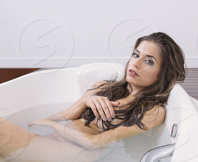 naked woman in white ceramic bath tub photo