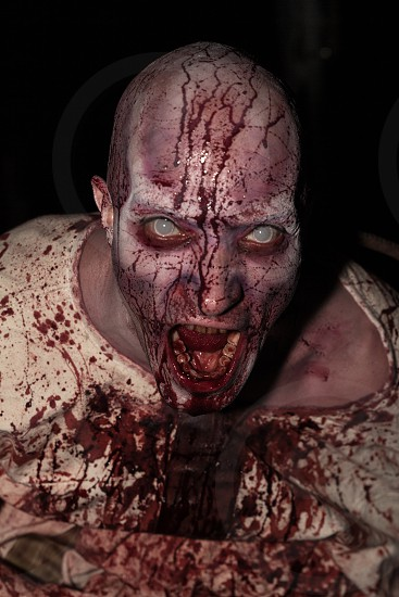 zombie man wearing grey contact lenses and bloody straight jacket photo