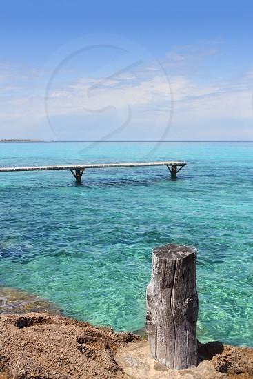 Formentera Illetes turquoise sea wooden pier aged trunk Illetas photo