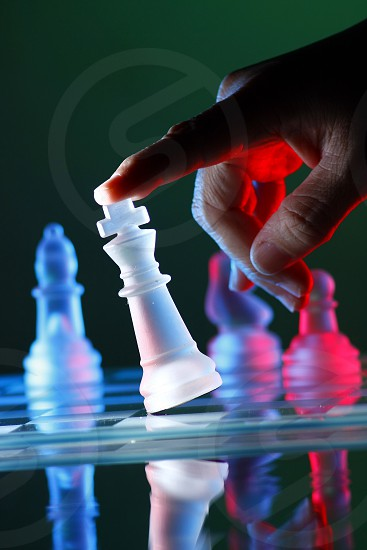 Finger tilting a chess piece of a glass chess set.  glass chess board game chess piece colorful red blue king queen bishop knight horse rook tower indoor game sport strategy tactics plan planning concede defeat lose loser fail failure photo