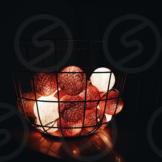 white and red baubles in black metal basket during nighttime photo