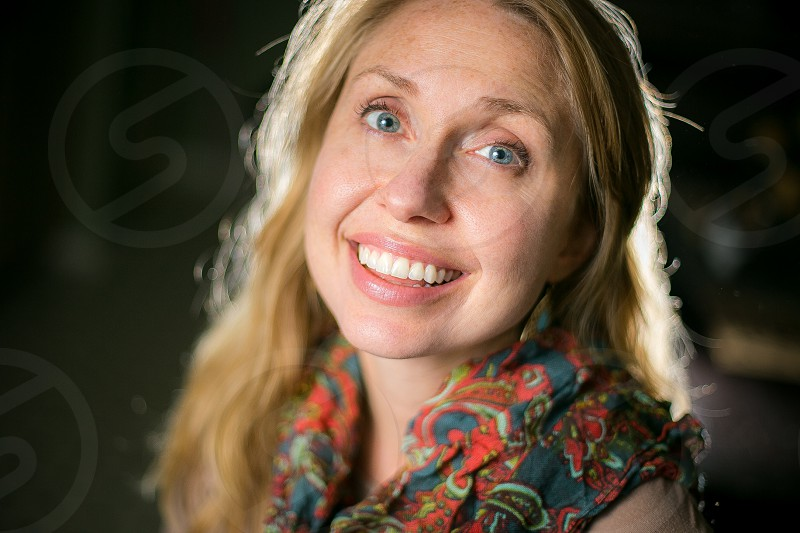 A beautiful young woman with long strawberry blond hair earrings and a colorful paisley scarf smiling in front of a clean dark background. photo