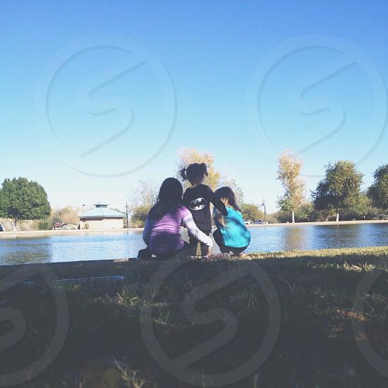 3 children sitting near pool photo
