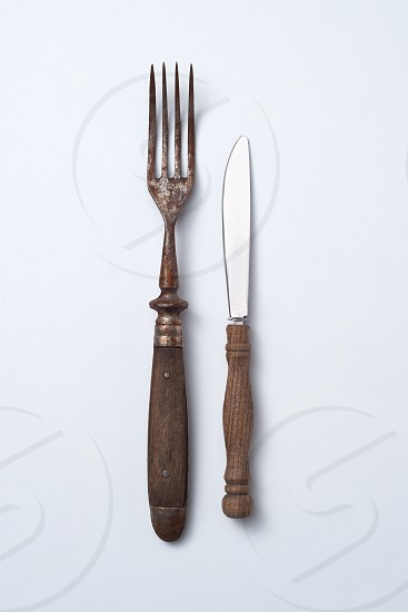 Cutlery fork and vintage knife with wooden handles on a gray background with space for text. Flat lay photo