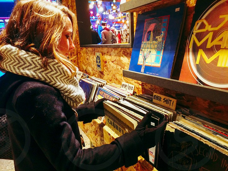 woman in grey white chevron scarf looking though records at record store photo