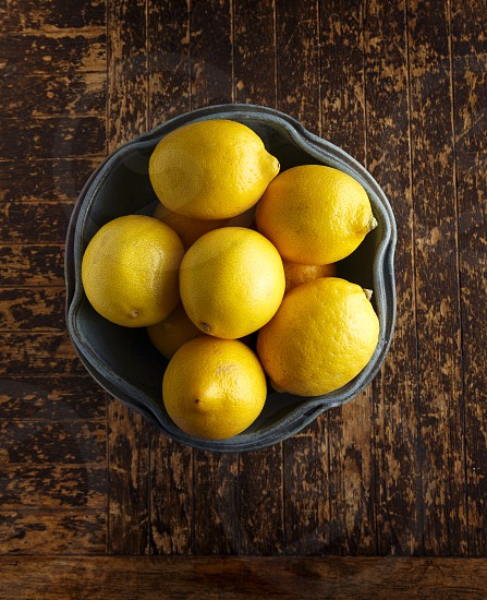 Bowl of Lemons on Rustic Wooden Surface photo