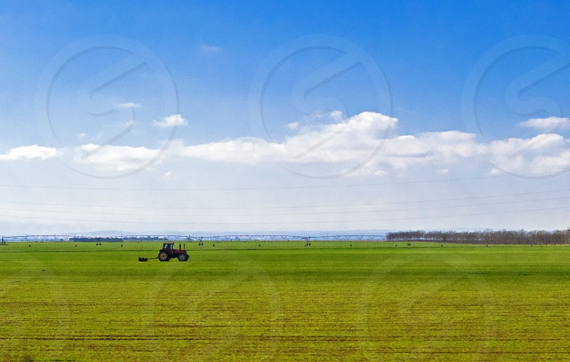 tractor in green field over blue cloudy sky gather crops in summer or autumn photo
