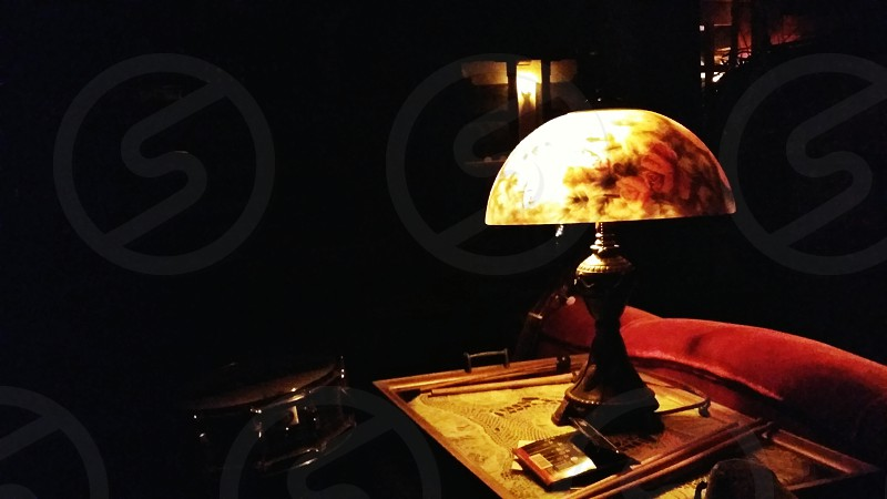 Night interior dark office Noir lamp vintage spooky eerie warm cabin detective red couch suspense photo