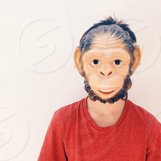 Boy monkeying around in a monkey mask. photo