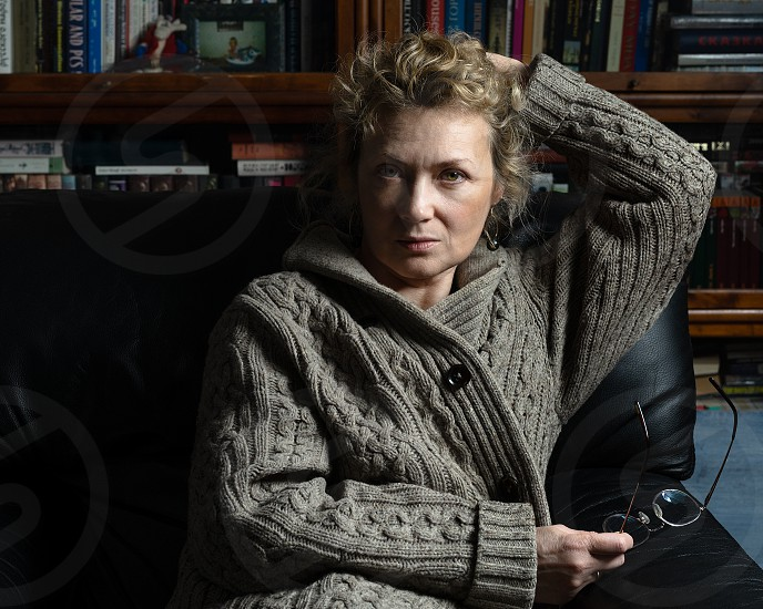 Studio shot of an adult woman with bookshelves as a background photo