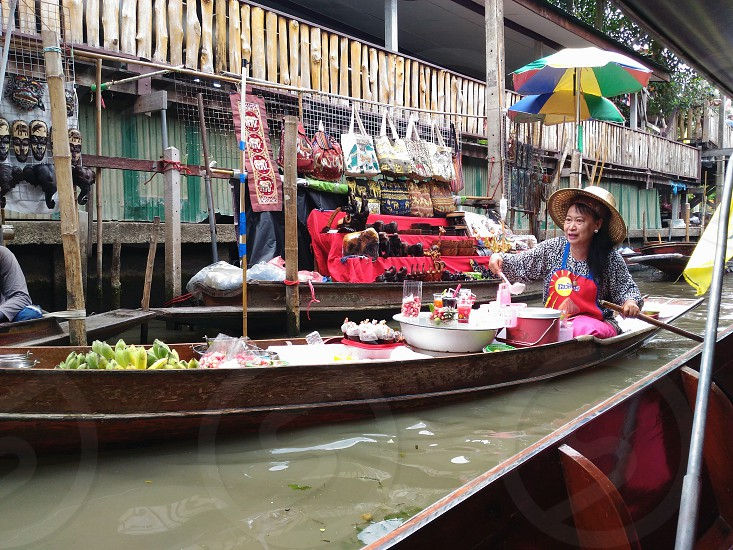 woman wearing blue long-sleeve top and brown hat on top of brown boat beside item lot photo