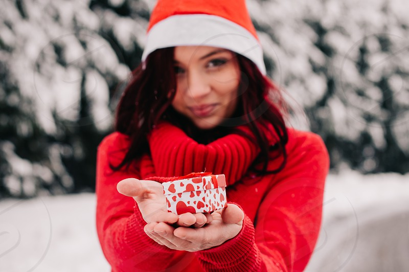 Young woman holding out small gift in christmas outfit. photo