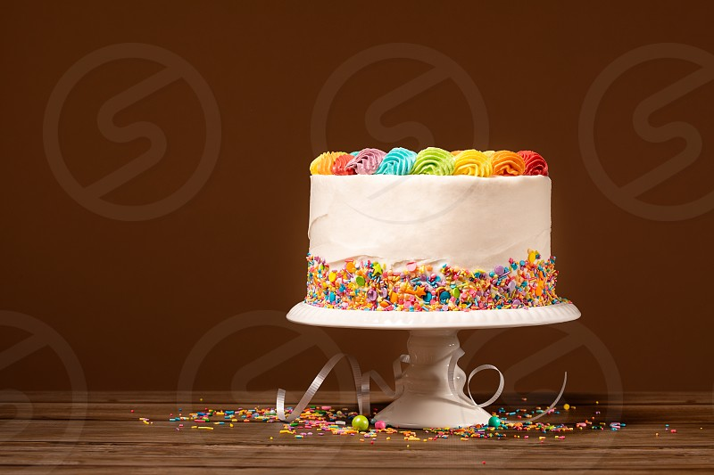 Birthday cake with rainbow icing and colorful sprinkles against a brown background. photo