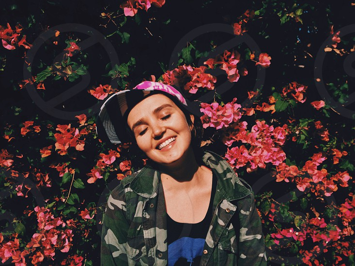 woman in pink black and white striped cap in black tee near red rose bush in camouflage jacket smiling photo
