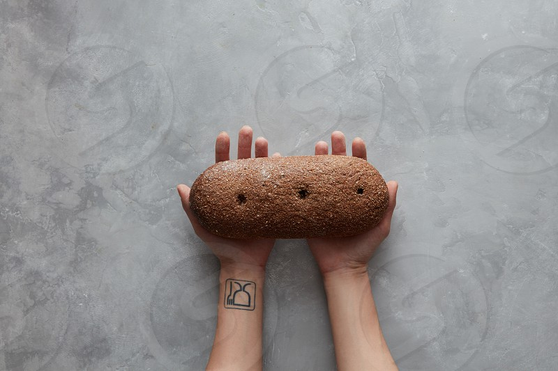 female hands holding brown loaf of bread on a gray stone background photo