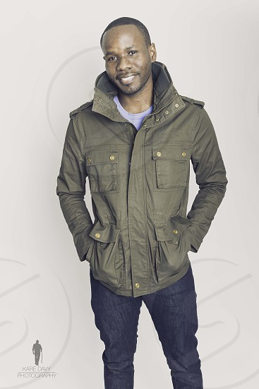 man in olive twill cargo parka with jeans against white walls hand in pocket photo