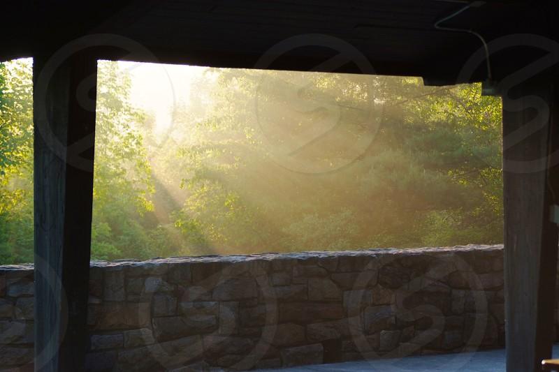 Rays of sunlight and stone wall. Pillars. Shelter. Morning. Vibrant. Brilliant. photo