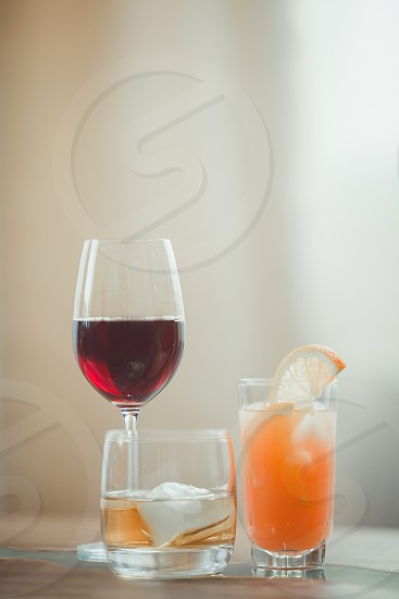 Drinks with red wine grapefruit cocktail and whisky. alcohol beverage citrus crystal drink drinks whiskey whisky wineglass Drinks wine glass red juice orange grapefruit ice cocktail bar evening whisky wooden wood photo