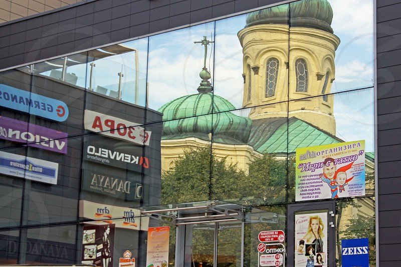Reflections in the entrance to a shopping mall of the Orthodox Cathedral of Saint Dimitar Vidin it is the second largest cathedral in Bulgaria. photo