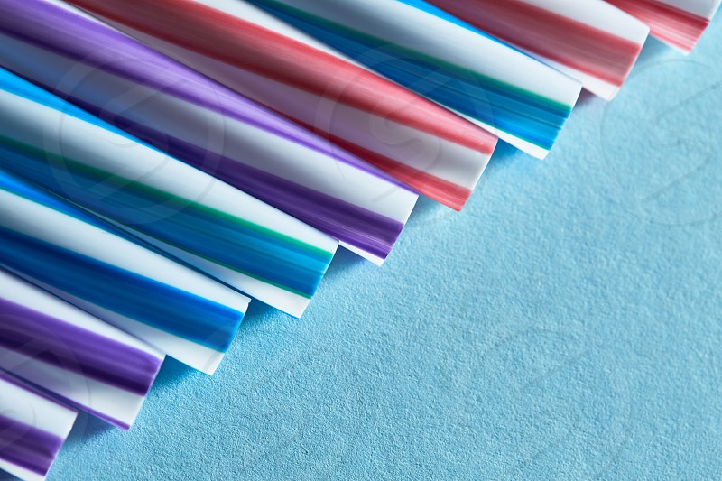 Blue purple and red plastic straws on a blue paper background. Copy space for text photo