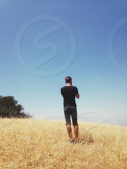 man standing on grass rolling field under clear blue sky photo