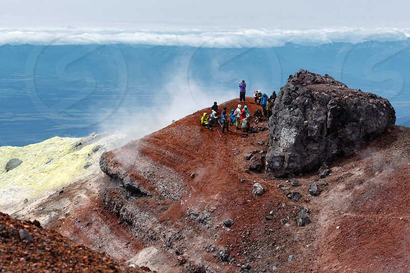 AVACHINSKY VOLCANO KAMCHATKA PENINSULA RUSSIAN FAR EAST - AUG 7 2014: Large group of tourists and travelers rests in summit crater of active Avacha Volcano after climbing to the top of volcano. photo