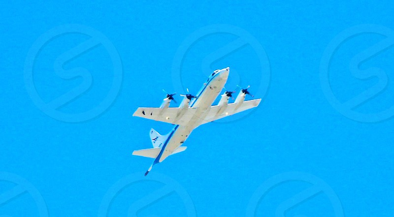 white and blue 4-propeller airplane flying during daytime photo