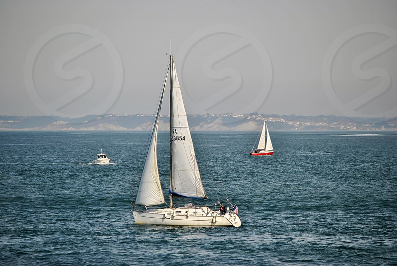2 sailing boats and power boat on ocean near island during daytime photo