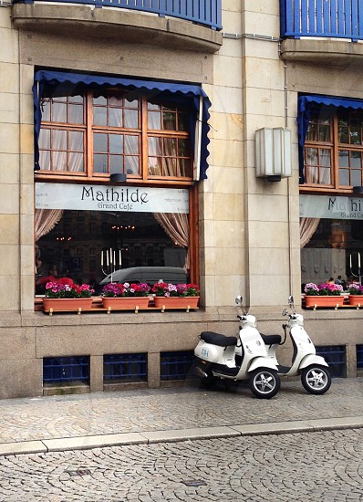 Old cafe in Belgian city royal blue accents flowers moped scooters photo