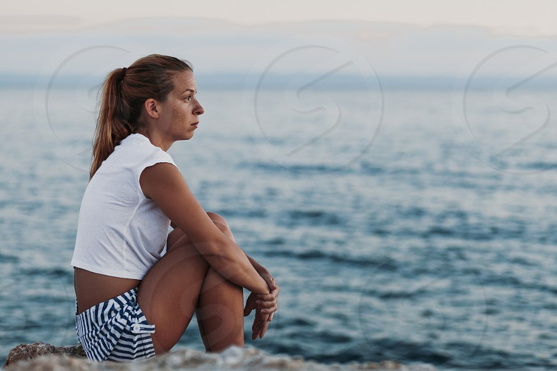 Woman sitting on the rock looking to the sea photo