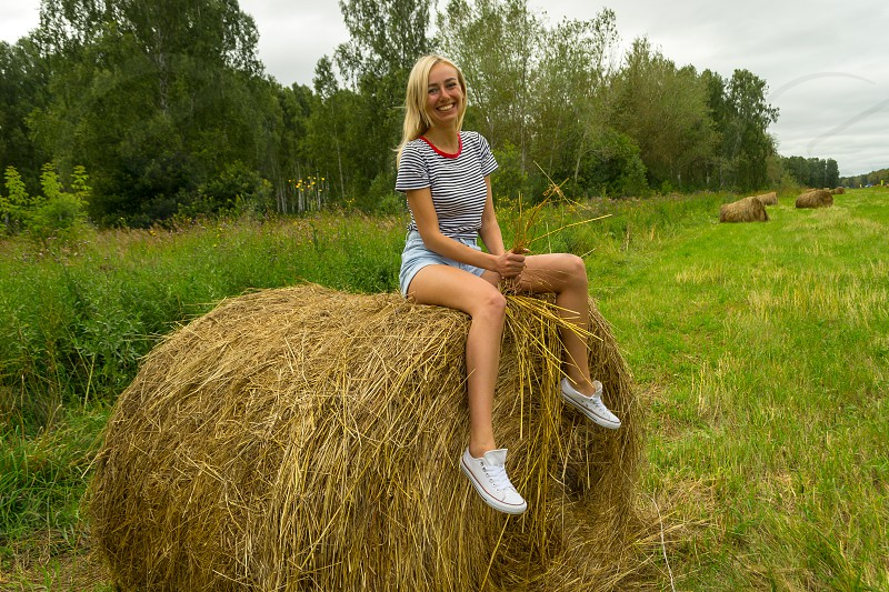 A beautiful blonde girl smiles and holds a bunch of grass between her legs and sits on a large round stack of dry hay collected smiling and on a summer or autumn afternoon photo