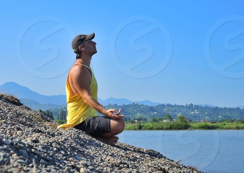 man in yellow tank top meditating photo
