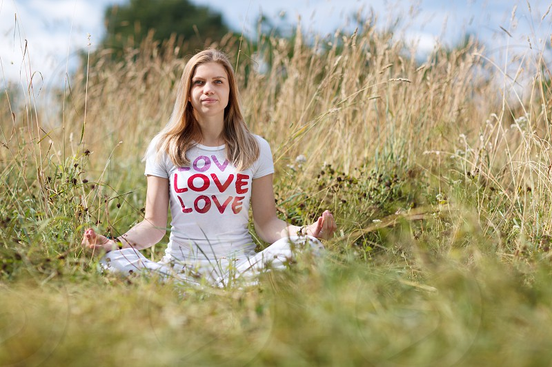 Young girl in white t-shirt meditating in the field photo