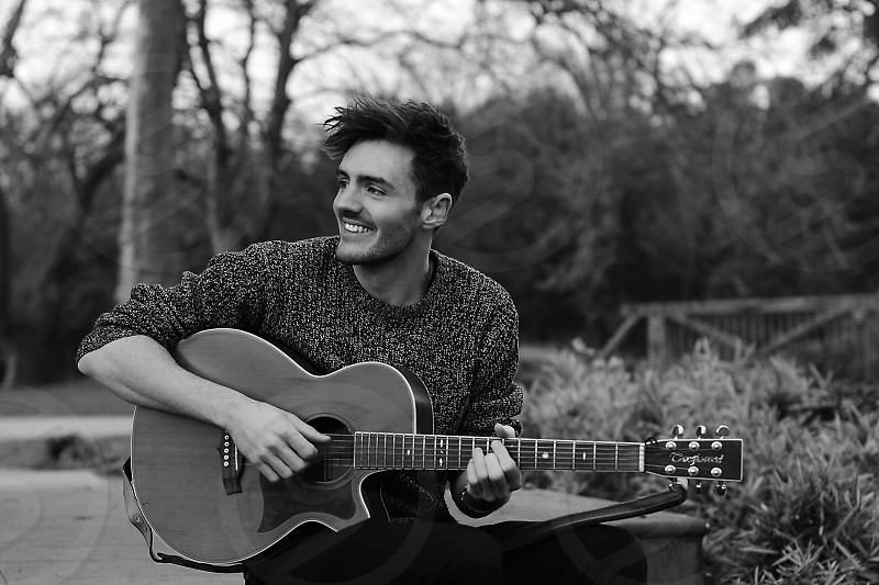 Man smiling playing guitar in the countryside photo