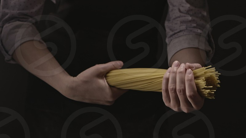 Girl's hands hold the bunch of raw uncooked italian pasta on a black background. Close-up. Slow motion Full HD video 240fps 1080p. Concept of italian food and cooking dinner. photo