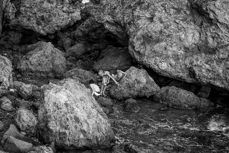 children playing on large rocks under a rock wall grayscale photo photo