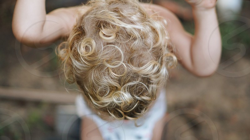 Curly blonde haired toddler looking down. photo