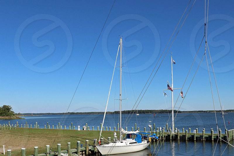 Small sailboat is moored a a dock photo