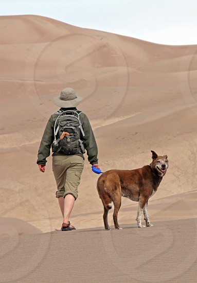 A hiker and dog at Great Sand Dunes National Park Colorado photo