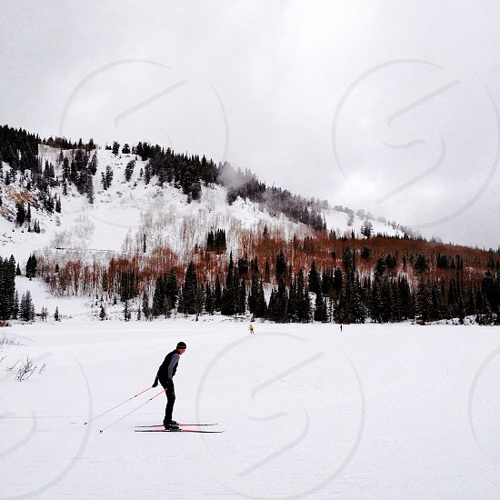 man skiing on snow covered field photo