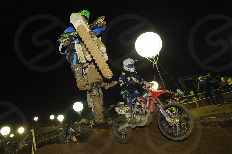 Jumping bike in motorcycle cross race in the night shot in Italy photo