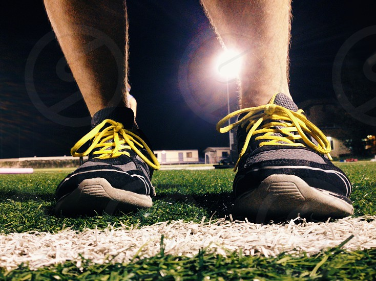 human feet in sneakers on grass field photo