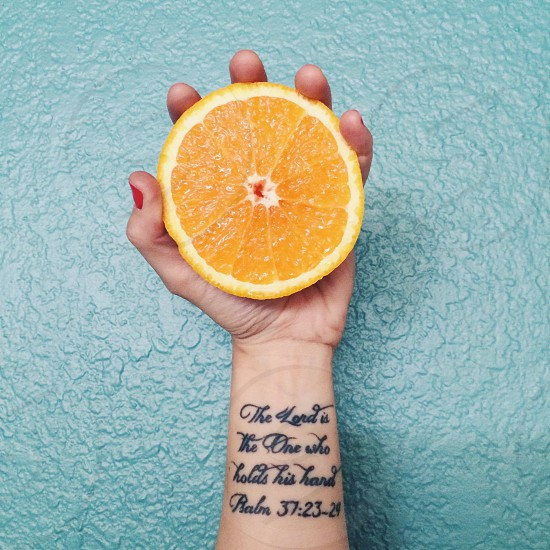 women holding sliced orange fruit photo