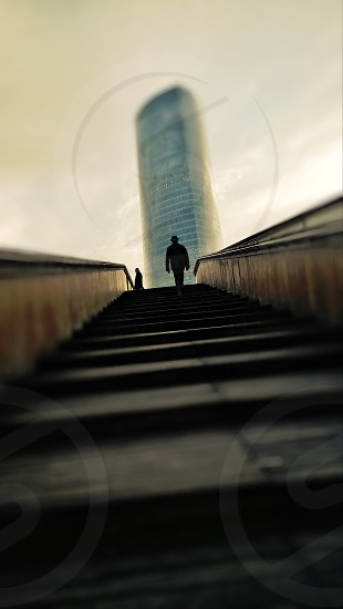 Solitary man walking towards Iberdrola tower in Bilbao. Building designed by Cesar Pelli. photo